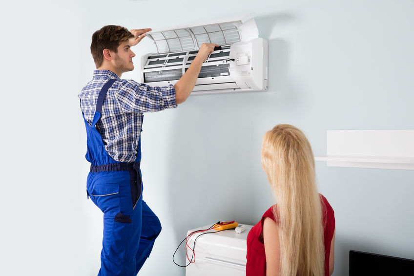 Technician Repairing Air Conditioner At Home